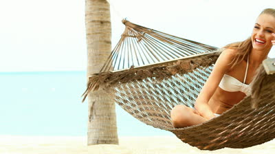 stock-footage-beautiful-smiling-woman-with-long-blonde-hair-sitting-cross-legged-in-a-hammock-at-the-beach